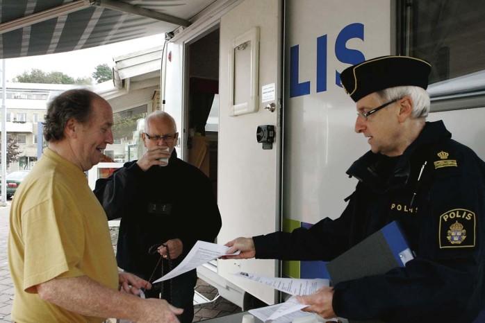 Lars-Åke Ringström delar ut information om det mobila poliskontoret, som kommer att finnas på plats i Lilla Edet varje torsdag.