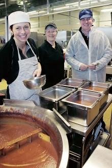 484 liter köttfärssås. Britt Jönsson slevar upp den färdiga köttfärssåsen i stålkantiner som sedan ska in i kylen. I bakgrunden syns kostchefen Anne-May Hugo och verksamhetschefen Tomas Nilsson.