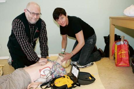 Eva Tilly utbildar Ica-handlare Stefan Vennberg hjärt- och lungräddning med hjärtstartare en så kallad defibrillator.