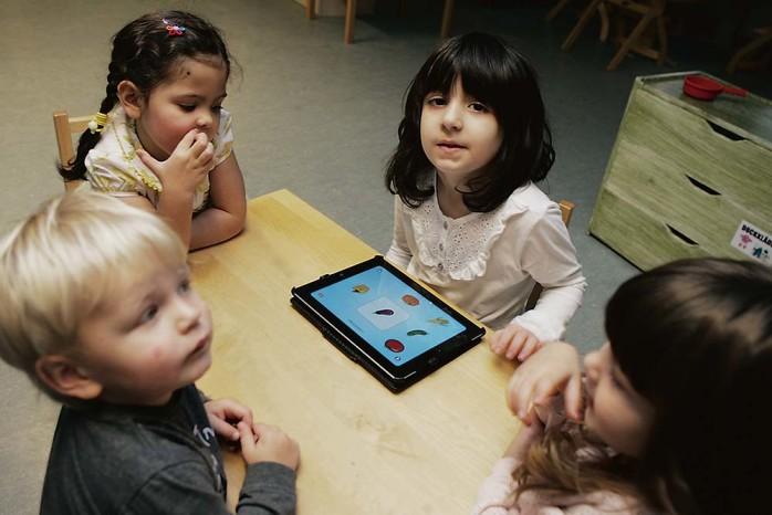 Samsas. Det är Novas tur att använda lärplattan och Lovisa, Filip och Andrea tittar nyfiket på.