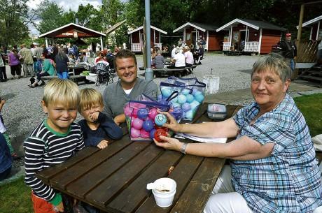 Jimmy Huhtala med barnen Hugo, 7 år, och Filip, 3 år, köpte bollar till Laxracet av Margareta Berggren.