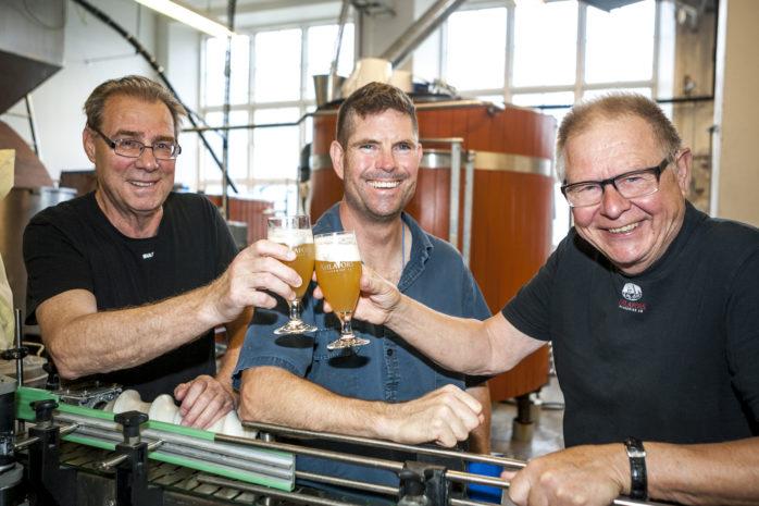"""Skål för Ahlafors Bryggeriers jubileumsipa! Mats Pihl och Christer """"Cralle"""" Sundberg hälsar samtidigt Jarrad Harrington välkommen i gänget. Jarrad arbetar två dagar i veckan som bryggare."""